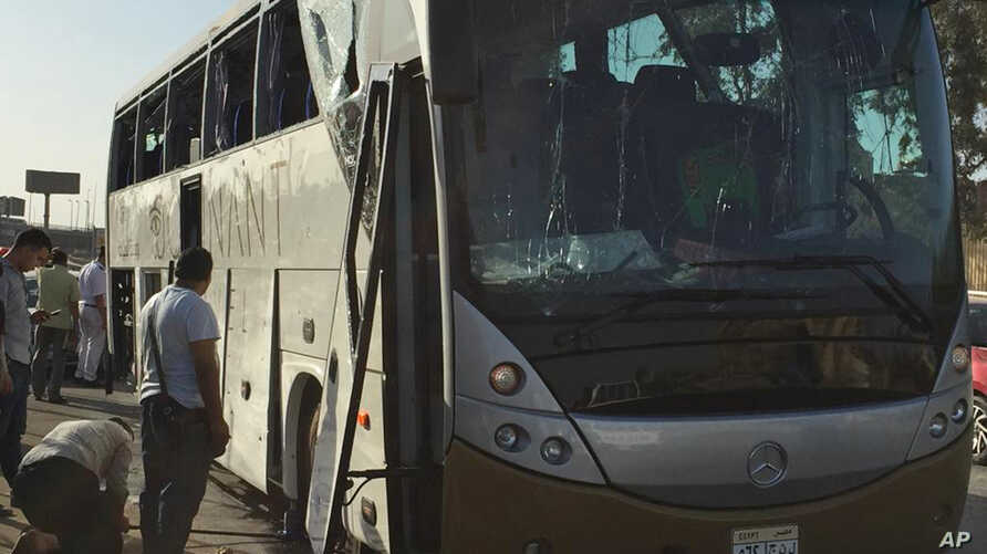 Officials jack up a bus that was damaged by a bomb, in Cairo, Egypt, Sunday, March 19, 2019. Egyptian officials say a roadside bomb has hit a tourist bus near the Giza Pyramids.