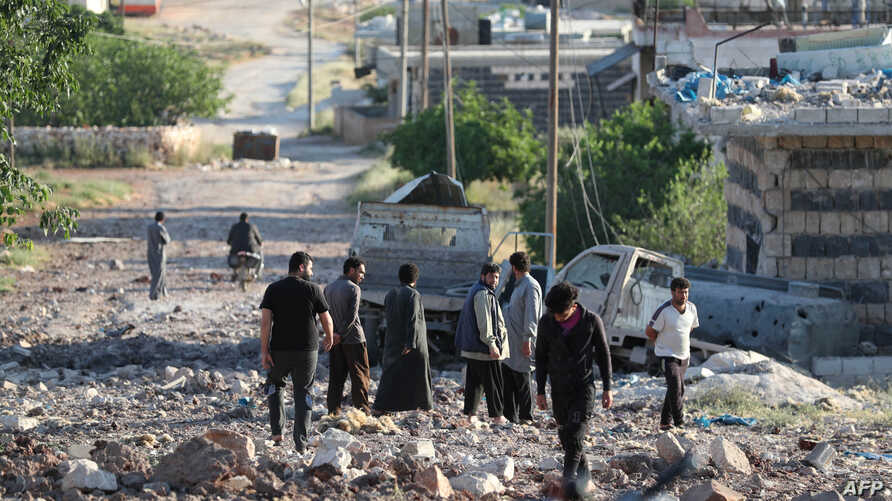 People gather amidst the rubble and damaged vehicles following reported air strikes by the Syrian regime ally Russia, in the town of Kafranbel in the rebel-held part of the Syrian Idlib province on May 20, 2019.