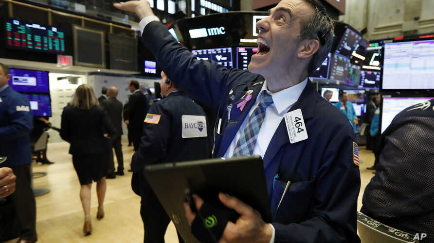 Trader Gregory Rowe reacts with fellow traders as he works on the floor of the New York Stock Exchange, May 1, 2019.