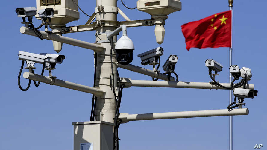 FILE - A Chinese national flag flutters near surveillance cameras mounted on a lamp post in Tiananmen Square in Beijing, March 15, 2019.