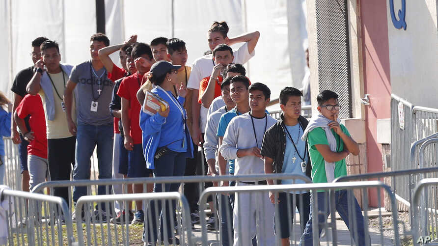 """FILE - Children line up to enter a tent at the Homestead Temporary Shelter for Unaccompanied Children in Homestead, Fla., April 19, 2019. Immigrant advocates say the U.S. government is allowing migrant children to languish in """"prisonlike conditions..."""
