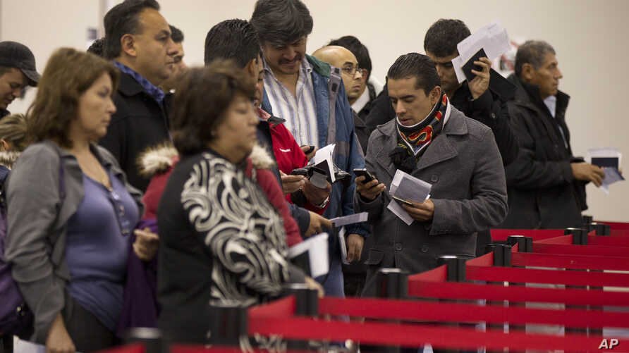 FILE - Nonresident visitors to the United States wait in line at immigration control after arriving at McCarran International Airport, in Las Vegas, Dec. 13, 2011.