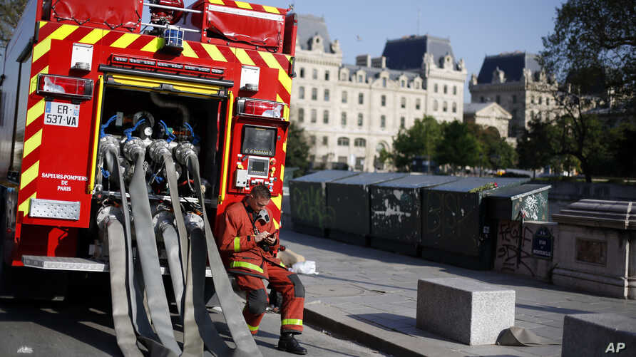 A firefighter checks his phone as he rests near the Notre Dame cathedral, in Paris, April 19, 2019.