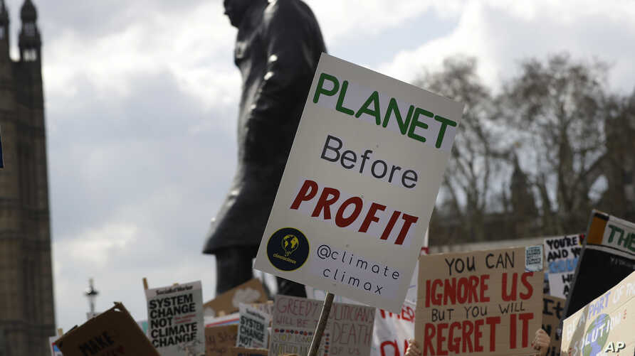 FILE - Climate change demonstrators hold banners in front of the Winston Churchill Statue during a protest near Parliament in London, April 12, 2019.