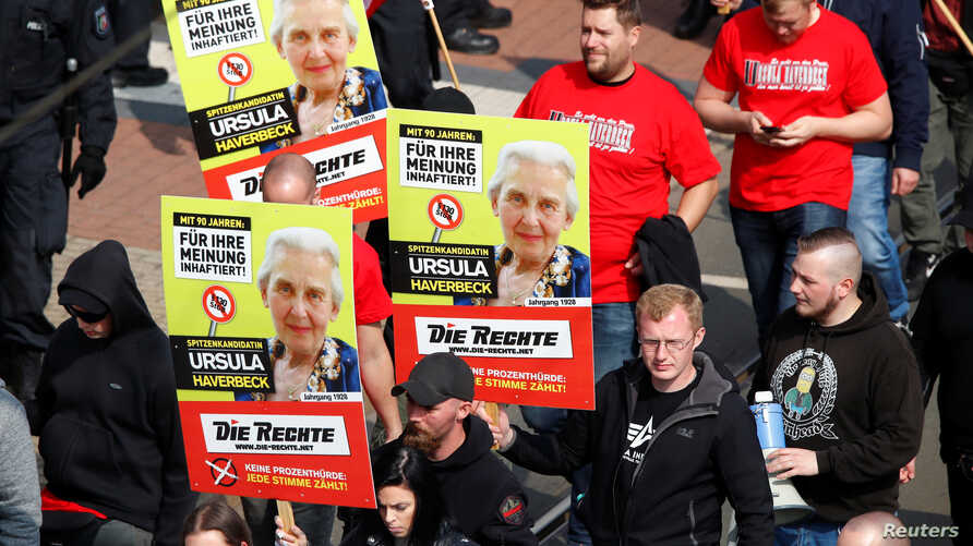 "Far-right supporters of the party ""Die Rechte (The Rights) carry placards of 90-year-old Ursula Haverbeck, who is imprisoned for her denial of the Holocaust during their May Day rally through the streets of Duisburg, Germany, May 1, 2019."