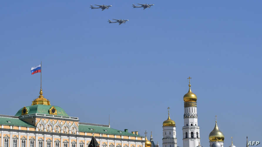FILE - Russian Tupolev Tu-95 turboprop-powered strategic bombers fly over the Kremlin in Moscow on May 7, 2019, during a rehearsal for the Victory Day military parade.