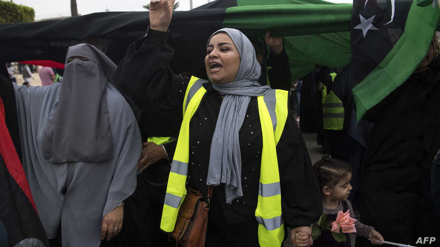 Libyans women, some wearing yellow vests, carry national flags as they chant slogans during a demonstration against strongman Khalifa Haftar in the capital Tripoli's Martyrs' Square on April 26, 2019.