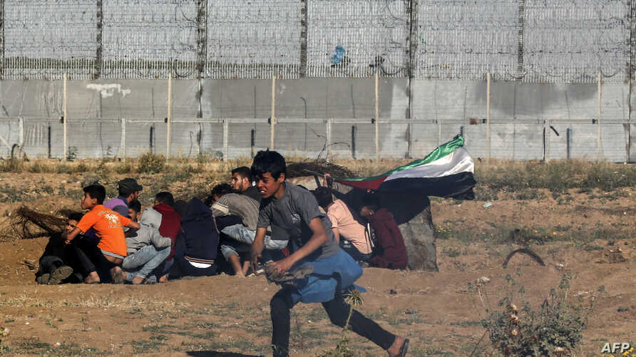Young Palestinian protesters run away from the border fence during a demonstration east of Gaza City, on May 10, 2019.