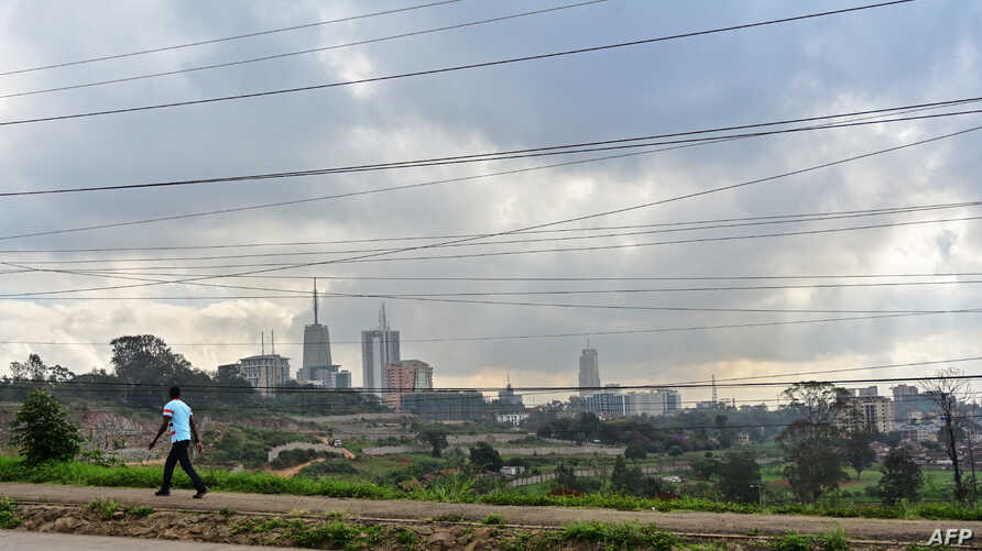 FILE - A section of Nairobi's city scape is seen May 16, 2019, through a crisscross of electrical lines as a man on his morning commute walks along Mbagathi Way in the Kenyan capital's southern sector.