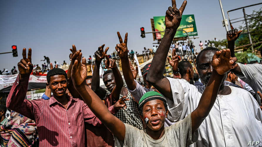 Sudanese protesters chant slogans and flash victory signs as they continue to demonstrate outside the army complex in  Khartoum, April 17, 2019. They hardened their demand that the military men in power quickly step down.
