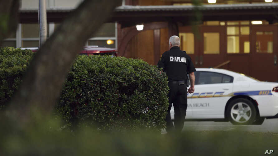 A police chaplain approaches the scene of shooting that killed 11 people in Virginia Beach, Va, May 31, 2019.
