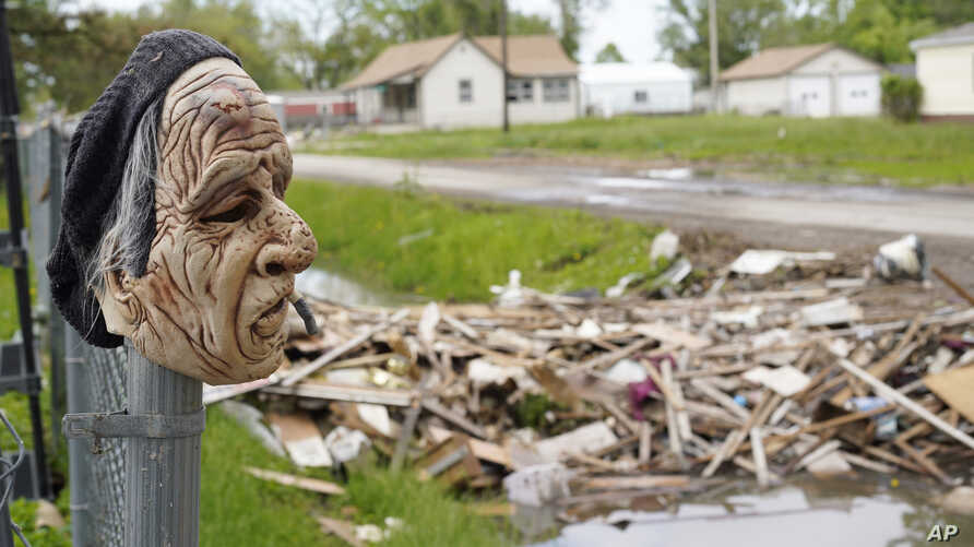 A mask hangs on a fence overlooking debris cleared out of one of many flood-damaged homes in Pacific Junction, Ia., May 24, 2019. Rep. Chip Roy, R-Texas, complaining of Washington's free-spending ways, has blocked a $19 billion disaster aid bill that...