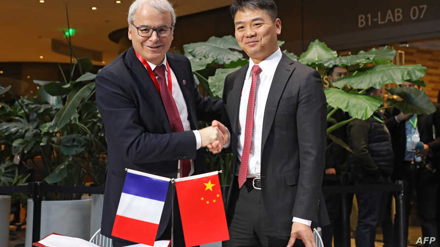 CEO of JD.com Richard Liu, right, shakes hands with Fives Group chairman Frederic Sanchez after signing an agreement during a meeting with business leaders and a visit by French President Emmanuel Macron at start-up incubator Soho3Q in Beijing, Jan. ...