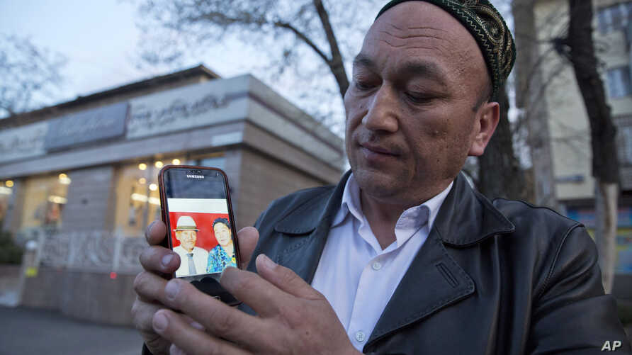 In this March 31, 2018, photo, Omir Bekali holds up a mobile phone showing a photo of his parents whom he believes have been detained in China, in Almaty, Kazakhstan.
