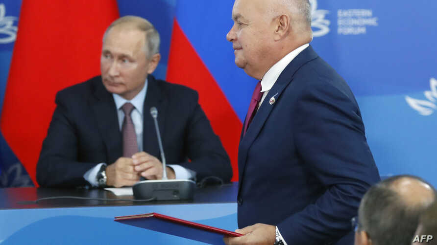 Russia's state news agency Rossiya Segodnya head Dmitry Kiselyov and Russian President Vladimir Putin attend a signing ceremony following the Russian-Chinese talks on the sidelines of the Eastern Economic Forum in Vladivostok, Sept. 11, 2018.