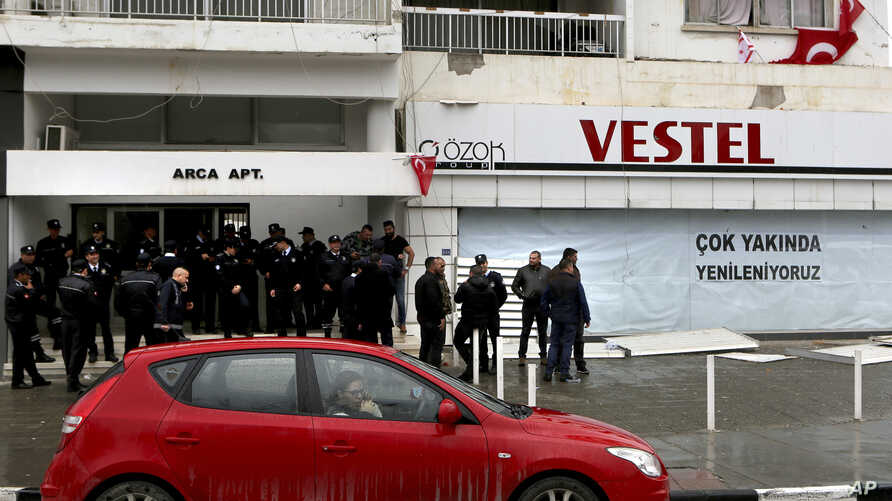 Police officers stand guard outside of the building of the Afrika newspaper office after it was attacked by supporters of the Turkish President Recep Tayyip Erdogan in the Turkish occupied northern part of the divided capital Nicosia, Cyprus, Jan. 22...