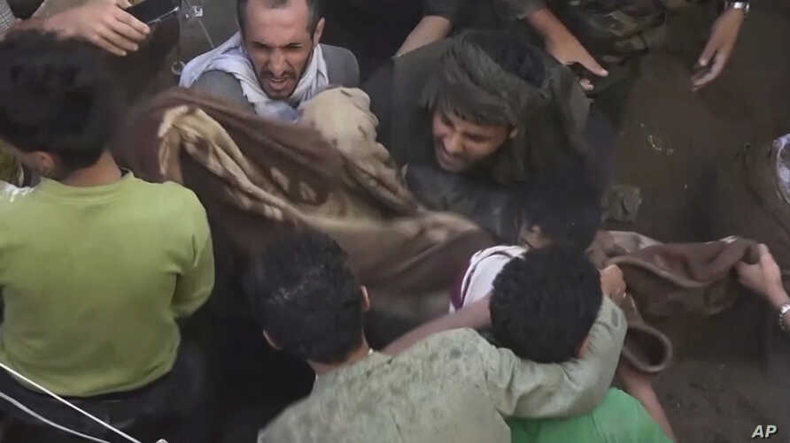 In this image taken from video, people carry a child's body after pulling it out from rubble following Saudi-led coalition airstrikes that killed dozens, including four children, officials said, in the residential center of the capital, Sanaa, Yemen,...