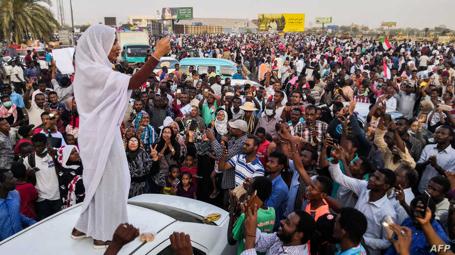 FILE - Alaa Salah, a Sudanese woman propelled to internet fame earlier this week after clips went viral of her leading powerful protest chants against President Omar al-Bashir, addresses protesters during a demonstration in front of the military head...