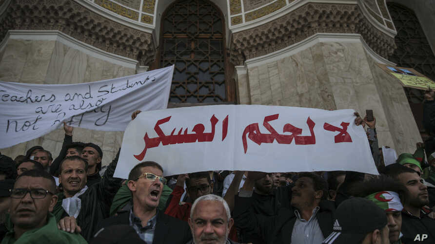 People chanting slogans raise banners rejecting military rule during a demonstration in Algiers, Algeria, April 10, 2019.