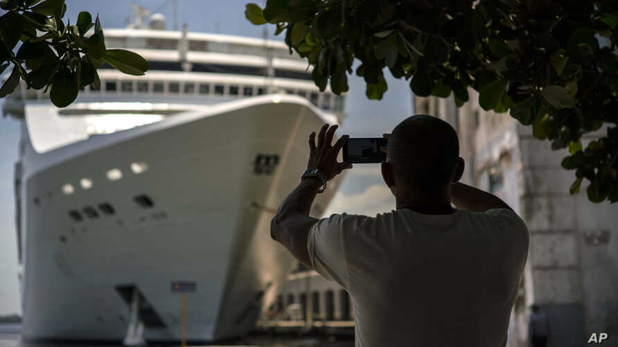 In this June 17, 2017, file photo, a man takes a photo of a cruise ship in Havana harbor, Cuba. President Donald J. Trump's new policy on Cuba travel bans Americans from doing business with entities controlled by Cuban military and intelligence agencies, including some 50 hotels. Hotels aren't an issue for cruises because passengers sleep onboard.