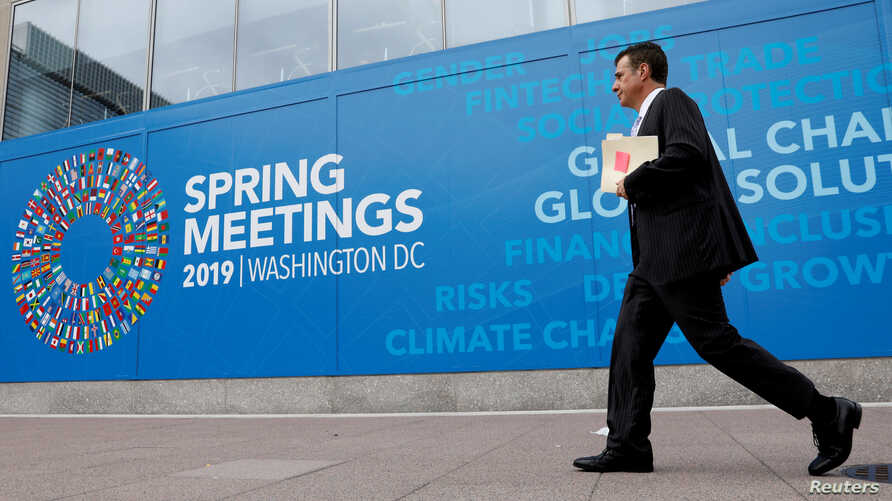 FILE - A man walks outside the International Monetary Fund headquarters building ahead of the IMF/World Bank spring meetings in Washington,  Apr. 8, 2019.