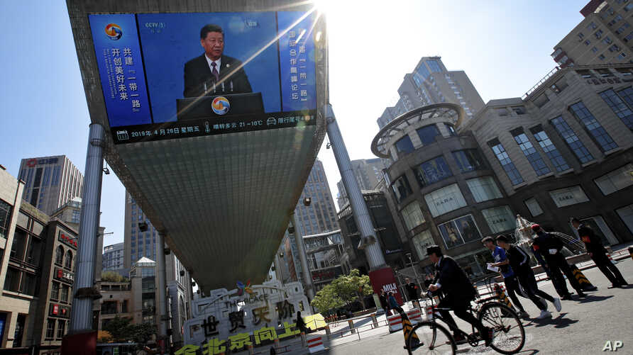People pass by a TV screen broadcasting live President Xi Jinping's opening speech, outside a shopping mall in Beijing, April 26, 2019.