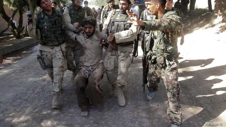 Afghan security forces escort a captured suspected Taliban insurgent during an operation in Sorkhrod district of Jalalabad province, June 19, 2013.