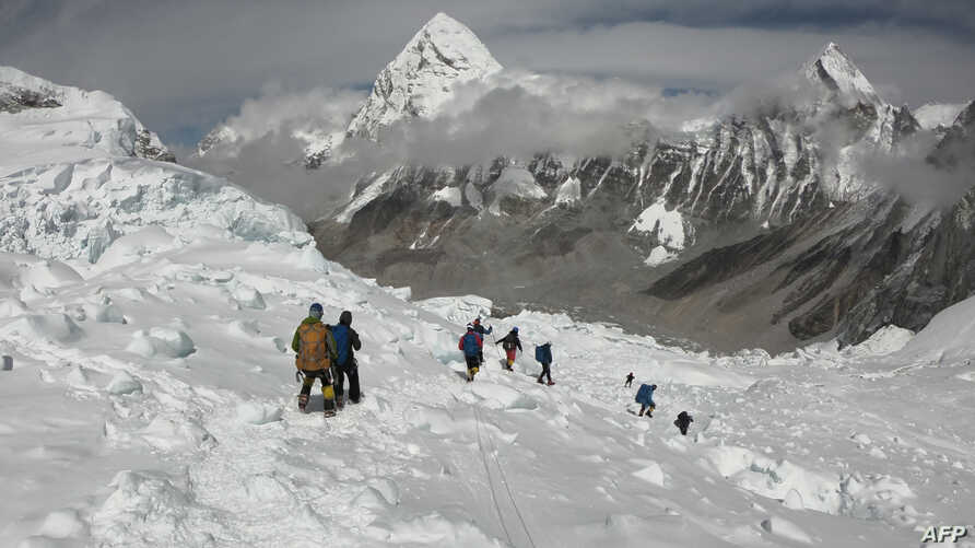 FILE - Mountaineers walk near Camp One of Mount Everest, April 29, 2018, as they prepare to ascend on the south face from Nepal.