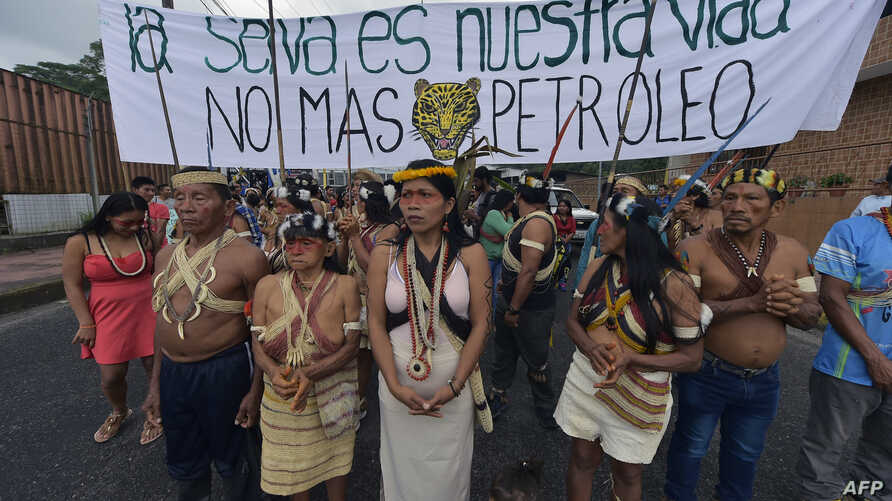 "Waorani indigenous people march toward the provincial court to demand the non-exploitation of oil in their territory with a banner reading ""The forest is our life. No more oil,"" in Puyo, Ecuador, April 11, 2019."
