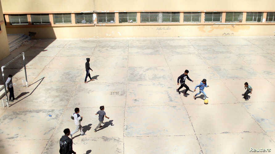 FILE - Libyan displaced boys, who fled their house because of the fighting between the Eastern forces commanded by Khalifa Haftar and the internationally recognised government, play soccer at Bader School, which is used as a shelter, in Tripoli, Liby...