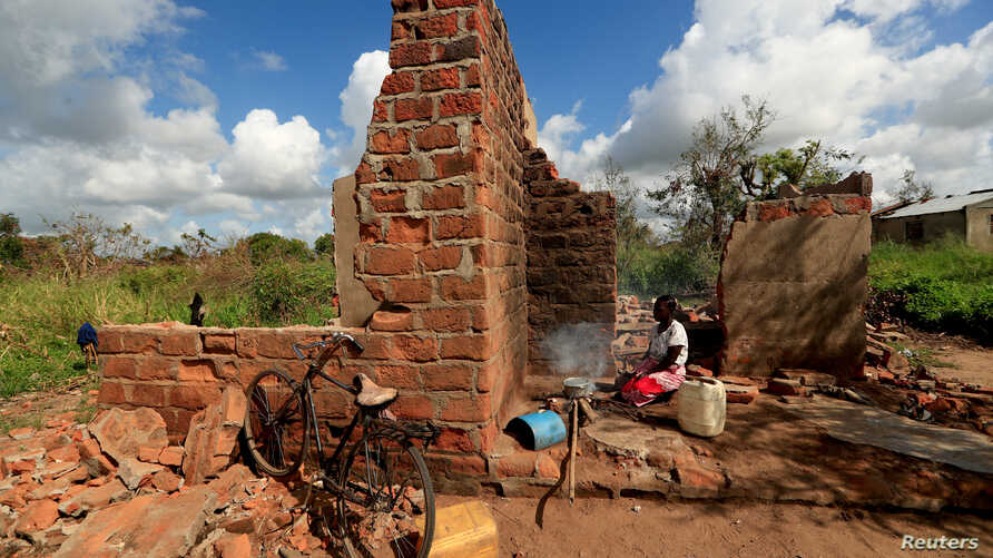 """Ester Thoma cooks at her damaged house in the aftermath of Cyclone Idai, in the village of Cheia, which means """"Flood"""" in Portuguese, near Beira, Mozambique April 1, 2019."""