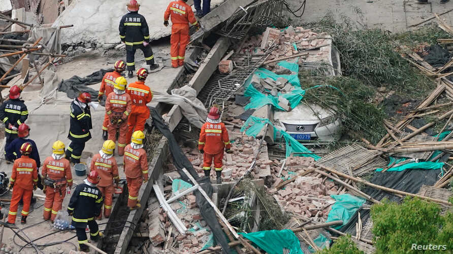 Firefighters work at the site of a collapsed building in Shanghai, May 16, 2019.