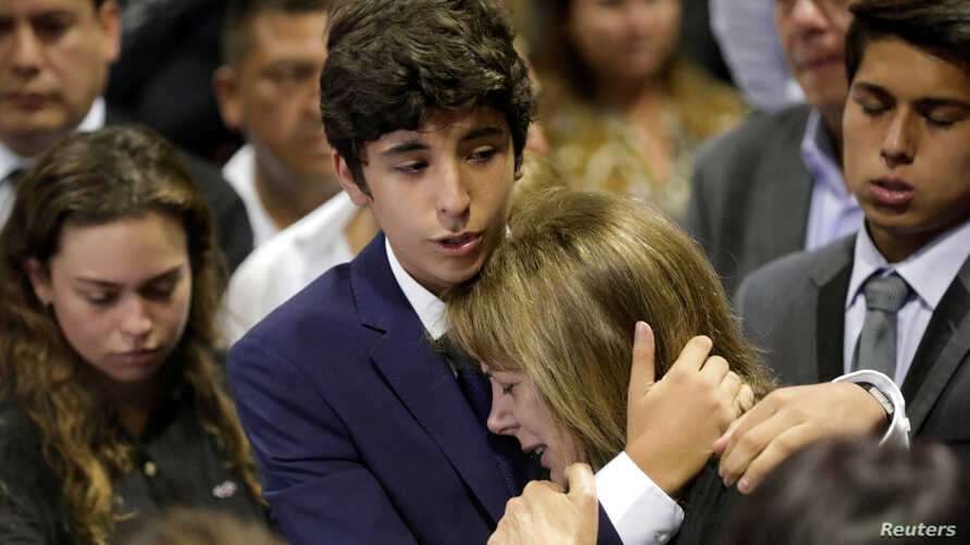 Federico Danton, son of Peru's former President Alan Garcia, hugs his mother Roxanne Cheesman during a wake for Garcia after he fatally shot himself on Wednesday, in Lima, Peru, April 17, 2019.
