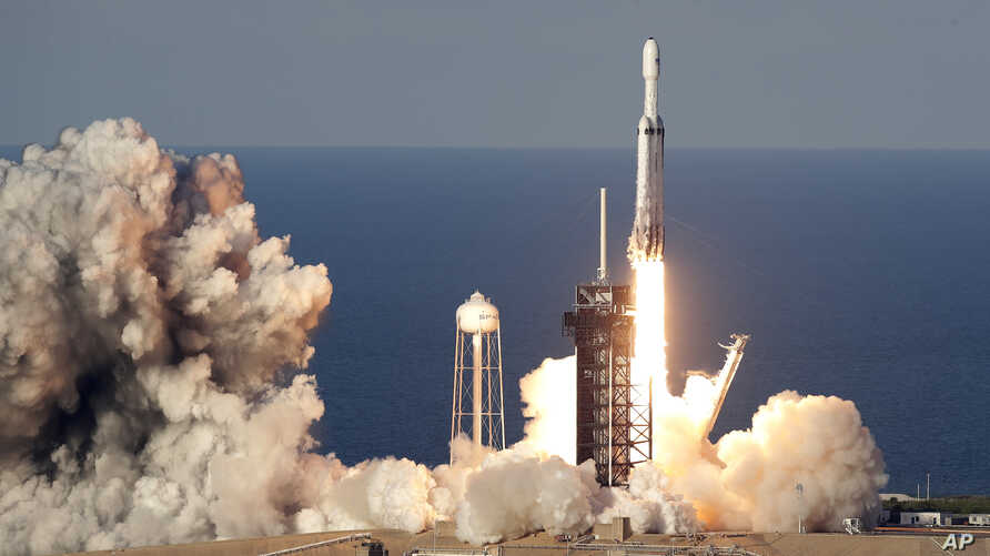 A SpaceX Falcon Heavy rocket carrying a communication satellite lifts off from pad 39A at the Kennedy Space Center in Cape Canaveral, Fla., April 11, 2019.