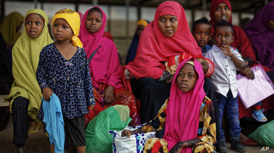FILE - Some of around 20 Somali refugee families wait to be flown to Kismayo in Somalia, under a voluntary repatriation program, at the airstrip of Dadaab refugee camp in northern Kenya, Dec. 19, 2017.