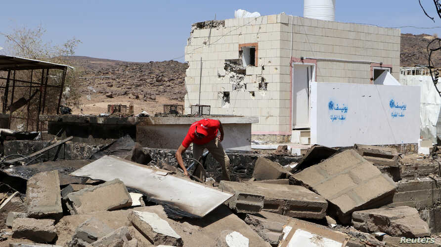 FILE - An aid worker searches the wreckage at the scene of an air strike that hit a gas station near a hospital in Kutaf district of the northwestern province of Saada, Yemen, March 28, 2019.