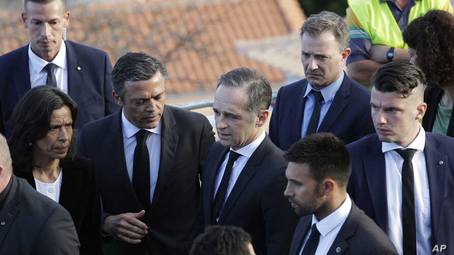 German Foreign Minister Heiko Maas, center, visits near the scene where a bus crashed in Canico, on Portugal's Madeira Island, April 18, 2019.