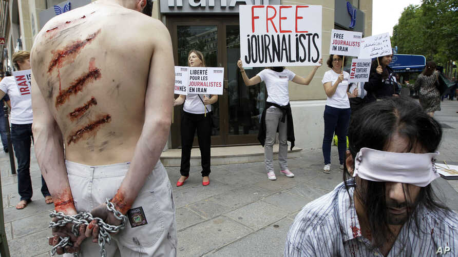 FILE - Reporters Without Borders activists, bound and made up as mock victims, demonstrate outside the Iran Air office on the Champs Elysées in Paris, July 10, 2012, to protest the imprisonment of Iranian journalists.