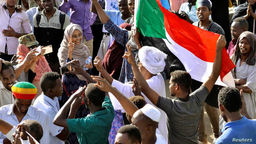 Sudanese demonstrators celebrate after Defense Minister Awad Ibn Auf stepped down as head of the country's transitional ruling military council, as protesters demanded quicker political change, near the Defense Ministry in Khartoum, Sudan, April 13, ...