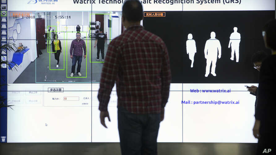FILE - Watrix employees demonstrate their firm's gait-recognition software at their company's offices in Beijing, Oct. 31, 2018.