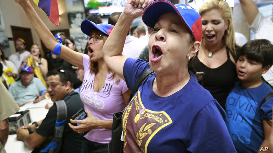 Arelys Lopez, foreground, leads a cheer as Venezuelans chant while watching televised news from their country at the El Arepazo Doral Venezuelan restaurant in Doral, Fla., April 30, 2019.
