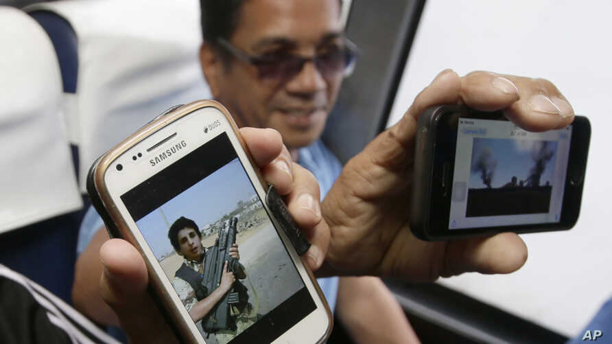 Overseas Filipino workers show photos taken with their cellphones of an armed Libyan rebel and the war-torn Benghazi in Libya upon arrival at the Ninoy Aquino International Airport in the Philippines, after being repatriated Aug. 4, 2014. The Philipp...
