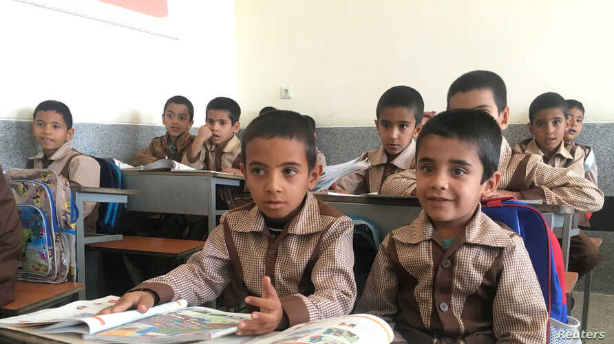FILE - Iranian and Afghan boys study in a classroom at the Be'sat school in Kerman, Iran, Oct. 23, 2016.