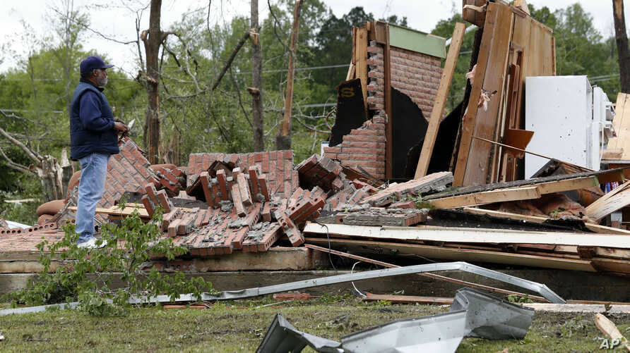 A friend of the owner reviews the remains of a storm damaged house in Morton, Miss., April 19, 2019, following a possible tornado touchdown Thursday afternoon.