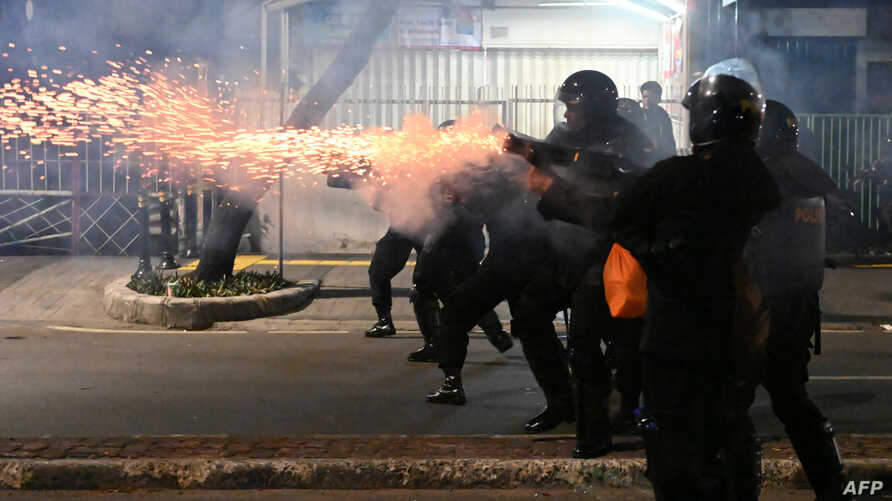 Indonesian police officers shoot tear gas to disperse protesters during a demonstration outside the Elections Oversight Body in Jakarta, May 22, 2019.