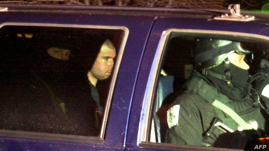 FILE - U.S.-Taliban fighter John Walker Lindh, 2nd left, rides in the back seat with security officers as they arrive at the Alexandria Detention Center in Alexandria, Virginia, Jan. 23, 2002.