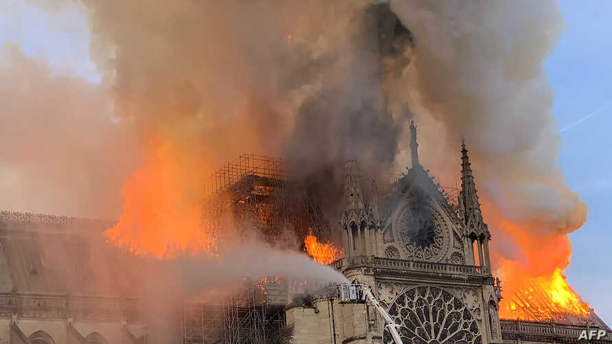 Flames and smoke are seen billowing from the roof at Notre-Dame Cathedral in Paris on April 15, 2019.