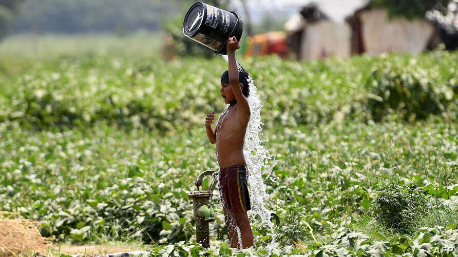 An Indian boy pours water on himself as he tries to cool himself off amid rising temperatures in New Delhi, May 29, 2019. Temperatures pushed toward 50 degrees Celsius across much of India on June 1.