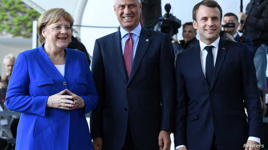 German Chancellor Angela Merkel, left, and French President Emmanuel Macron welcome Kosovo's President Hashim Thaci, center, to a meeting with Western Balkans leaders, at the Chancellery in Berlin, Germany, April 29, 2019.