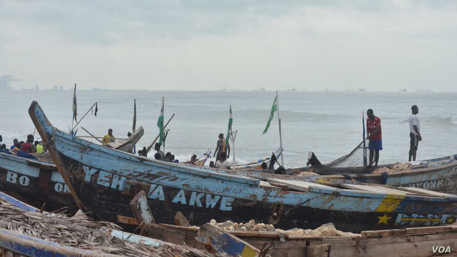 Fishermen in the Nungua area of Accra wait for canoes to come in with their catches.  (S. Knott for VOA)